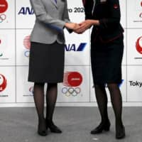 An All Nippon Airways (left) and Japan Airlines cabin attendant hands at Tokyo 2020 Olympic and Paralympic Games Official Partner ceremony in Tokyo in June 2015. ` | REUTERS