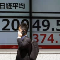 A man wearing a face mask to help curb the spread of the coronavirus walks past an electronic stock board showing Japan's Nikkei 225 index at a securities firm in Tokyo on Friday. Japan's largest business lobby plans to suggest that member companies introduce a four-day workweek as part of effort to reduce risks of infection. | AP