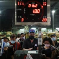 Buyers wearing face masks attend an auction of fruits and vegetables at a wholesale market in Taipei, on Thursday. The leaders of U.S. congressional foreign affairs committees have written to more than 50 countries asking them to support Taiwan's inclusion in the World Health Organization, citing the need for the broadest effort possible to fight the coronavirus pandemic. | REUTERS