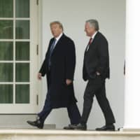 U.S. President Donald Trump and Mark Meadows, White House chief of staff walk to the Oval Office following a wreath-laying ceremony in Washington on Friday. The United States issued a new rule the same day tightening visa guidelines for Chinese journalists. | EPA / VIA BLOOMBERG