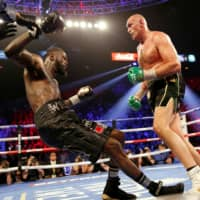 Tyson Fury knocks down Deontay Wilder during their fight on Feb. 22 in Las Vegas. | REUTERS