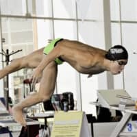 Katsuhiro Matsumoto jumps into the pool during a training camp in Mexico in February. | KYODO