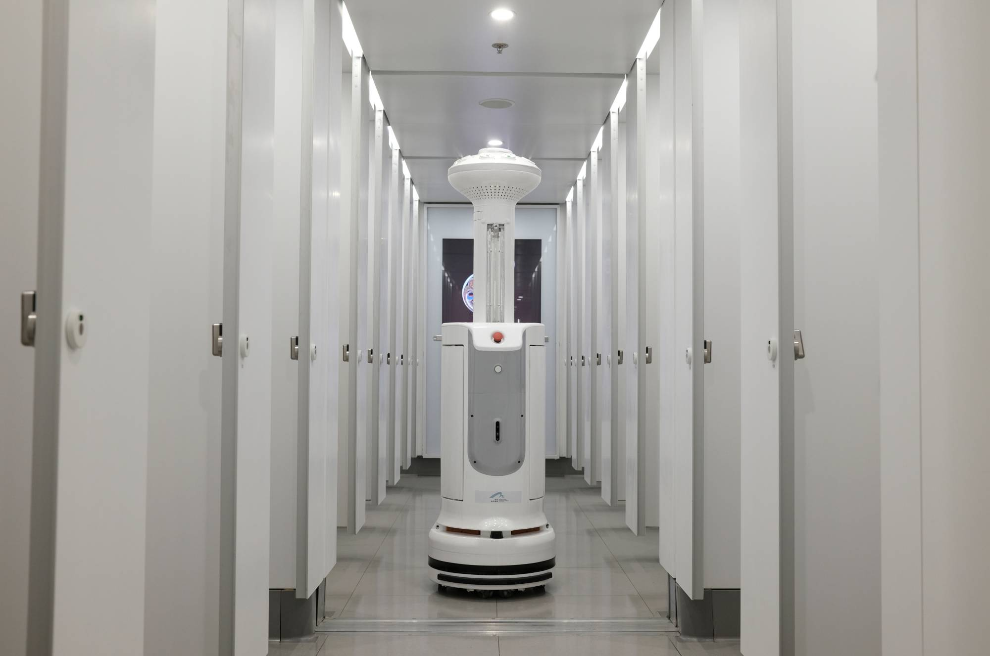 An Intelligent Sterilization Robot, produced by China's TMiRob, uses UV light to sanitize a bathroom amid the coronavirus pandemic, at Hong Kong International Airport on Thursday. Researchers in the city have found that patients suffering milder illness caused by the new coronavirus recover more quickly if they are treated with a three-drug antiviral cocktail soon after symptoms appear. | REUTERS