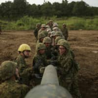 U.S. Marines and Ground Self-Defense Force troops clean the main gun's barrel of a Japanese tank at a live-fire range during the Northern Viper 17 exercises in Hokkiado in August 2017. | U.S. MARINE CORPS / VIA REUTERS