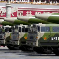 Military vehicles carrying DF-26 ballistic missiles travel past Tiananmen Gate during a military parade to commemorate the 70th anniversary of the end of World War II in Beijing in September 2015. | POOL / VIA REUTERS