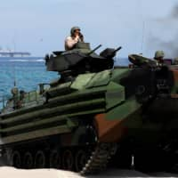 With the USS-Wasp in the background, U.S. Marines ride an amphibious assault vehicle during amphibious landing exercises, part of U.S.-Philippine war games promoting bilateral ties at a military camp in the Philippines' Zambales province in April last year. | REUTERS