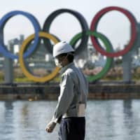 A masked construction worker stands in Tokyo's Odaiba waterfront district, with the Olympic rings in the background.  | AP