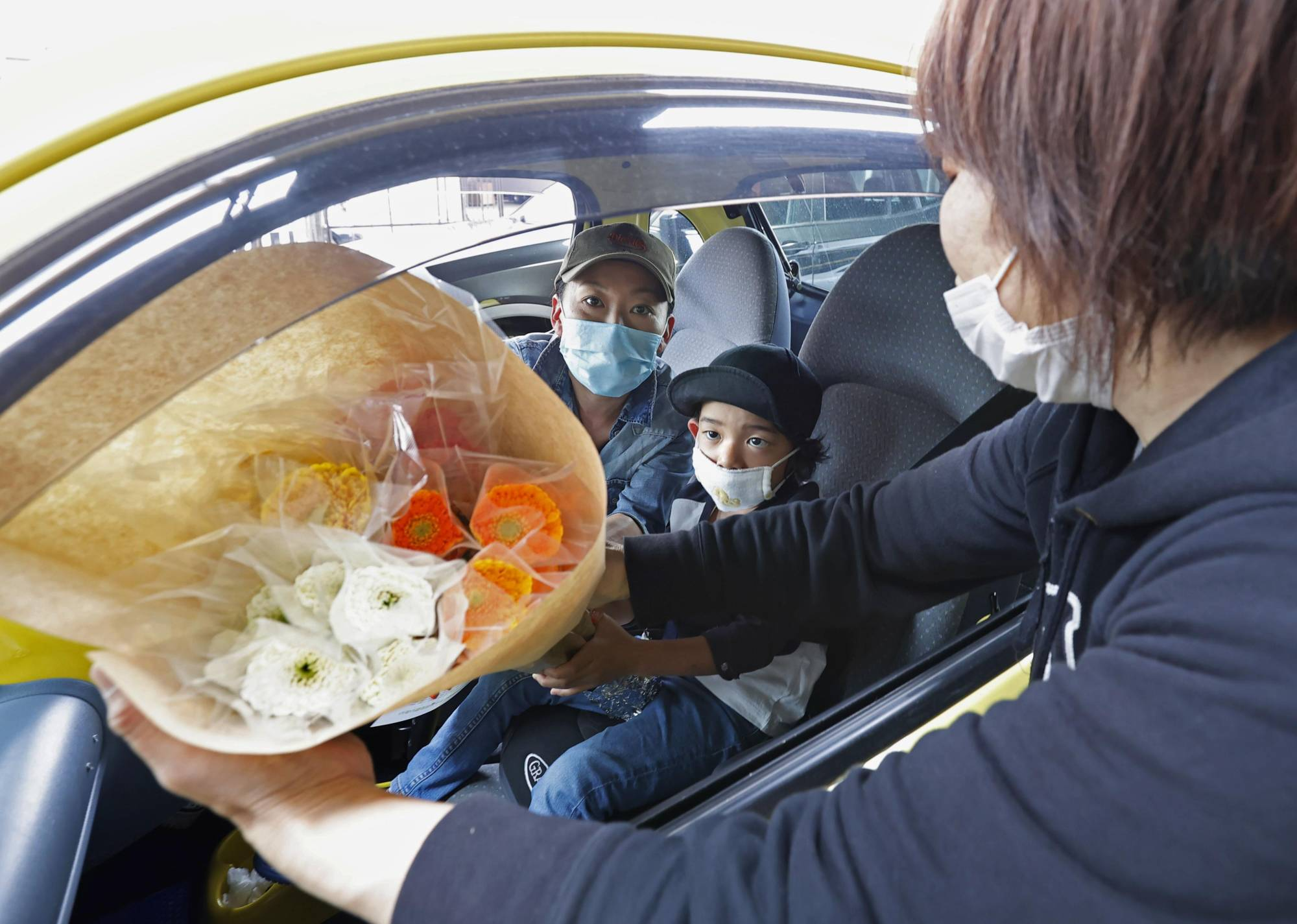 Customers pick up flowers for Mother's Day at a drive-thru service in Kawasaki on Saturday. | KYODO