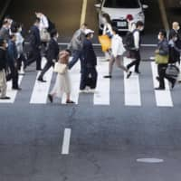 Commuters walk in Osaka's Umeda commercial district on Thursday, as they return to work after Japan's Golden Week holidays. | KYODO