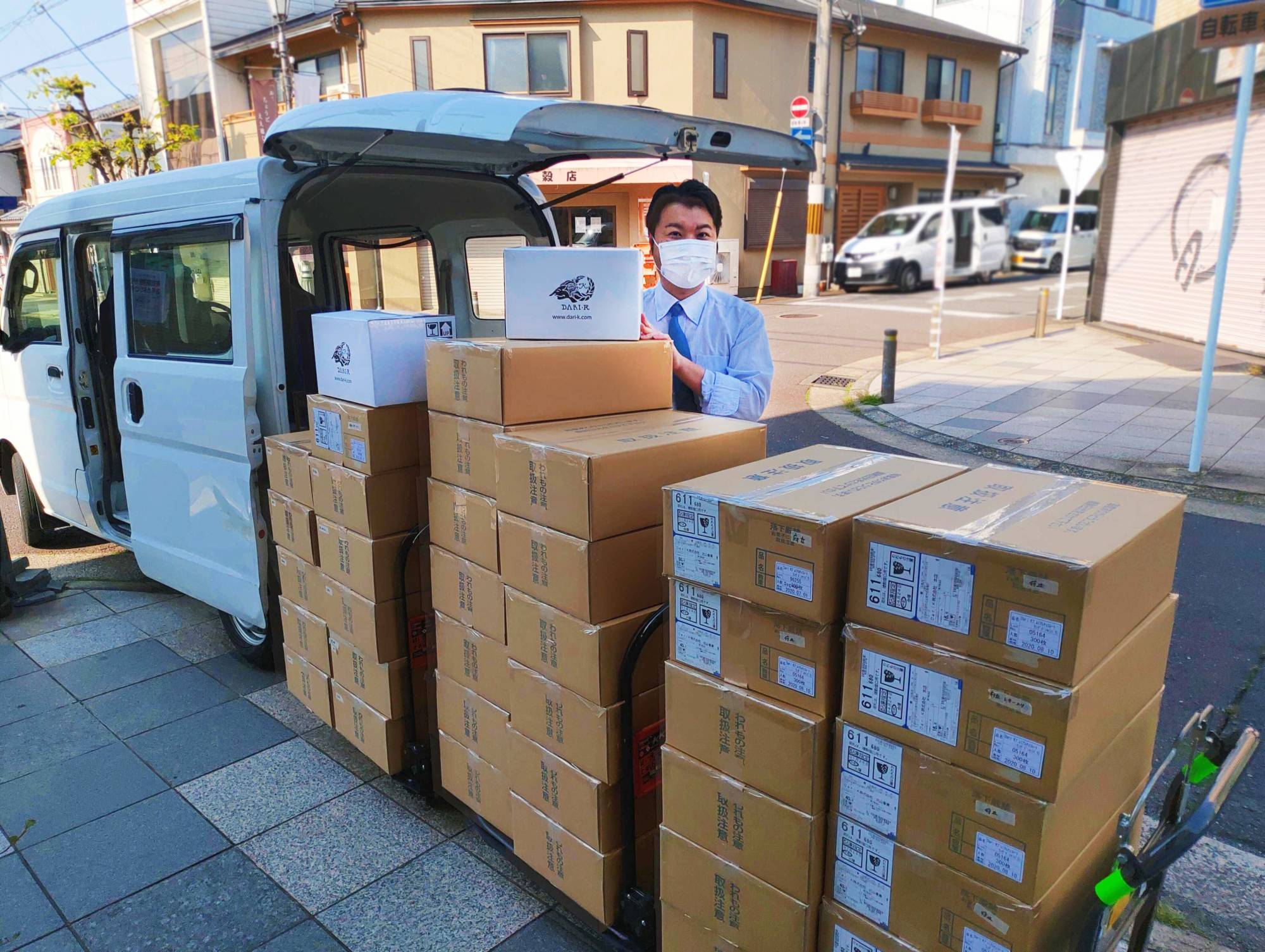 Keiichi Yoshino, president and CEO of Dari K Co., poses with boxes of chocolates bound for health care workers, in front of its main shop in Kyoto on April 30. | DARIK CO. / VIA KYODO