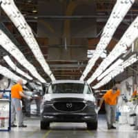 Workers inspect a Mazda Motor Corp. CX-5 sports utility vehicle on an assembly line at the Mazda Sollers Manufacturing Rus LLC plant in Vladivostok, Russia. | BLOOMBERG