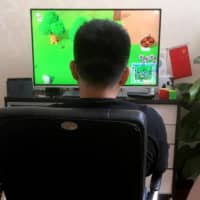 Chinese tutor Zhao Tianyu plays Animal Crossing on a Nintendo Switch at his apartment in Beijing in April.  | REUTERS