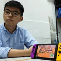 Hong Kong pro-democracy activist Joshua Wong poses with a Nintendo Switch, where depictions of anti-government protesters and signs reading 'Free Hong Kong' are seen in the game Animal Crossing.   | REUTERS