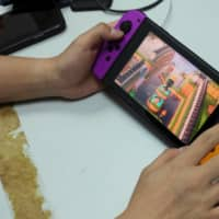 Depictions of Hong Kong Chief Executive Carrie Lam are seen in the game Animal Crossing as pro-democracy activists Joshua Wong demonstrates playing the game on a Nintendo Switch.  | REUTERS