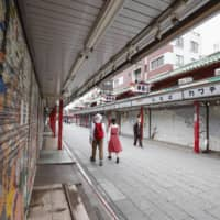 People walk past shuttered stores in Tokyo's Asakusa tourist area on Saturday amid an extended nationwide state of emergency over the coronavirus pandemic. | KYODO