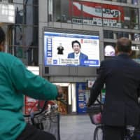 People watch a news conference by Prime Minister Shinzo Abe in which he explained the extension of a nationwide state of emergency over the coronavirus pandemic until the end of the month, in Osaka's Dotonbori district on May 4.  | KYODO