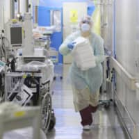 A staff member works in an intensive care unit at a hospital that treats COVID-19 patients in Kawasaki, Kanagawa Prefecture, in April. | KYODO