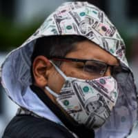 A man wears a mask as he participates in a 'Freedom Rally' protest in support of opening Florida, in South Beach in Miami on Sunday. | AFP-JIJI