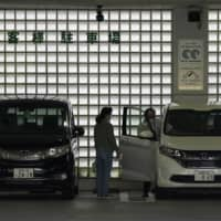 Honda Motor Co. vehicles are parked at a dealership in Tokyo on Sunday. | BLOOMBERG