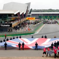 A Union Jack flag is carried onto the track by service personnel before the Formula One British Grand Prix on July 14 in Silverstone, England. | REUTERS