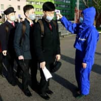 Students wearing face masks have their temperature checked as a precaution against the new coronavirus as their university reopened following vacation at the Kim Chaek University of Technology in Pyongyang on April 22. | AP