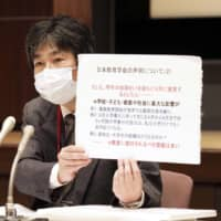Teruyuki Hirota, professor of education sociology at Nihon University, holds a news conference at the education ministry in Tokyo on Monday. | KYODO