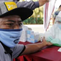 A health worker collects a man's blood sample for a coronavirus antibody test in Bali, Indonesia, on Monday. | AP