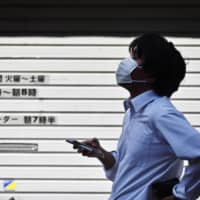 The government won't ask people to refrain from traveling between prefectures where COVID-19 infections are relatively low under a plan to revise the nation's emergency declaration. | AFP-JIJI