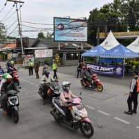 Motorists commute past a checkpoint during a partial lockdown to curb the spread of COVID-19 in Jakarta on Monday. | AFP