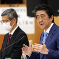 Prime Minister Shinzo Abe gestures as he speaks alongside Shigeru Omi, president of the Japan Community Healthcare Organization, during a news conference in Tokyo on May 4. | BLOOMBERG