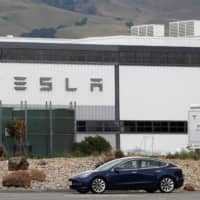 A Tesla vehicle drives past the company's primary vehicle factory in Fremont, California, after CEO Elon Musk announced he was defying local officials' coronavirus restrictions by reopening the facility Monday. | REUTERS