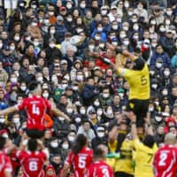 Fans wearing masks watch a Top League game between Hino and Suntory at Chichibunomiya Rugby Ground on Feb. 22. | KYODO