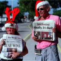People sell newspapers at a Hollywood, Florida, intersection on Dec. 14, 2000, announcing that George W. Bush had defeated Vice President Al Gore in the presidential race. | BLOOMBERG