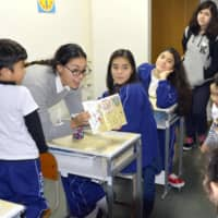 A teacher holds a Japanese-language lesson for Brazilian children of Japanese descent at a school in Toyota, Aichi Prefecture, in 2016. | KYODO