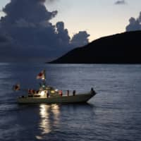 A fishing boat with hoisted Japanese national flags, sails around the Senkaku Islands in the East China Sea in September 2012.   REUTERS