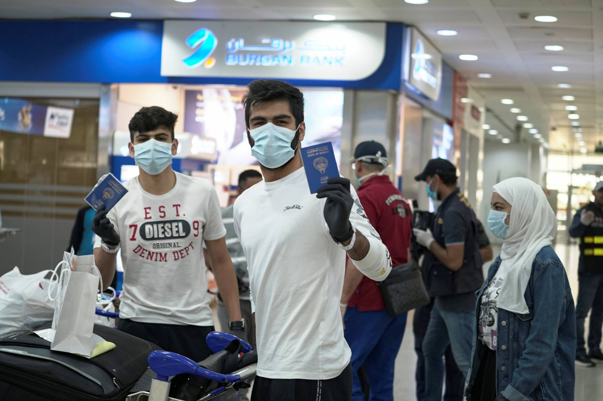 Right of passage: Young Kuwaitis arrive home from Jordan wearing face masks and quarantine tracking bracelets. | REUTERS