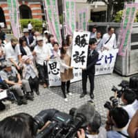 Small victory: Lawyers hold a banner reading 'victory' in front of the Kumamoto District Court last year after the court ordered the government to compensate the families of former leprosy patients who suffered discrimination.  | KYODO