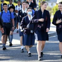 Students arrive for the first day of face-to-face schooling after a period of learning from home due to coronavirus precautions in Brisbane, Australia, on Monday. Australia's second-most populous state, Victoria, will resume in-person teaching May 27, weeks earlier than expected. | DAN PELED / VIA REUTERS