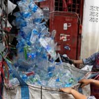 Women collect plastic bottles brought by a truck at a recycling plant in Bangkok on Monday. Environment Minister Varawut Silpa-archa has acknowledged a setback in the fight against plastic waste during the pandemic, but said he remained hopeful Thailand could still regain lost ground. | REUTERS