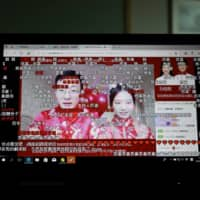 Liu Wenchao (left) and Sun Hanxiao get married in a ceremony that was livestreamed. In China — where livestreaming is extremely popular — young couples are allowing anyone to not only watch their big day online, but also send them cash gifts. | AFP-JIJI