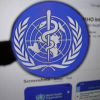 The logo for the World Health Organization WHO Info application is displayed on a computer screen. | BLOOMBERG