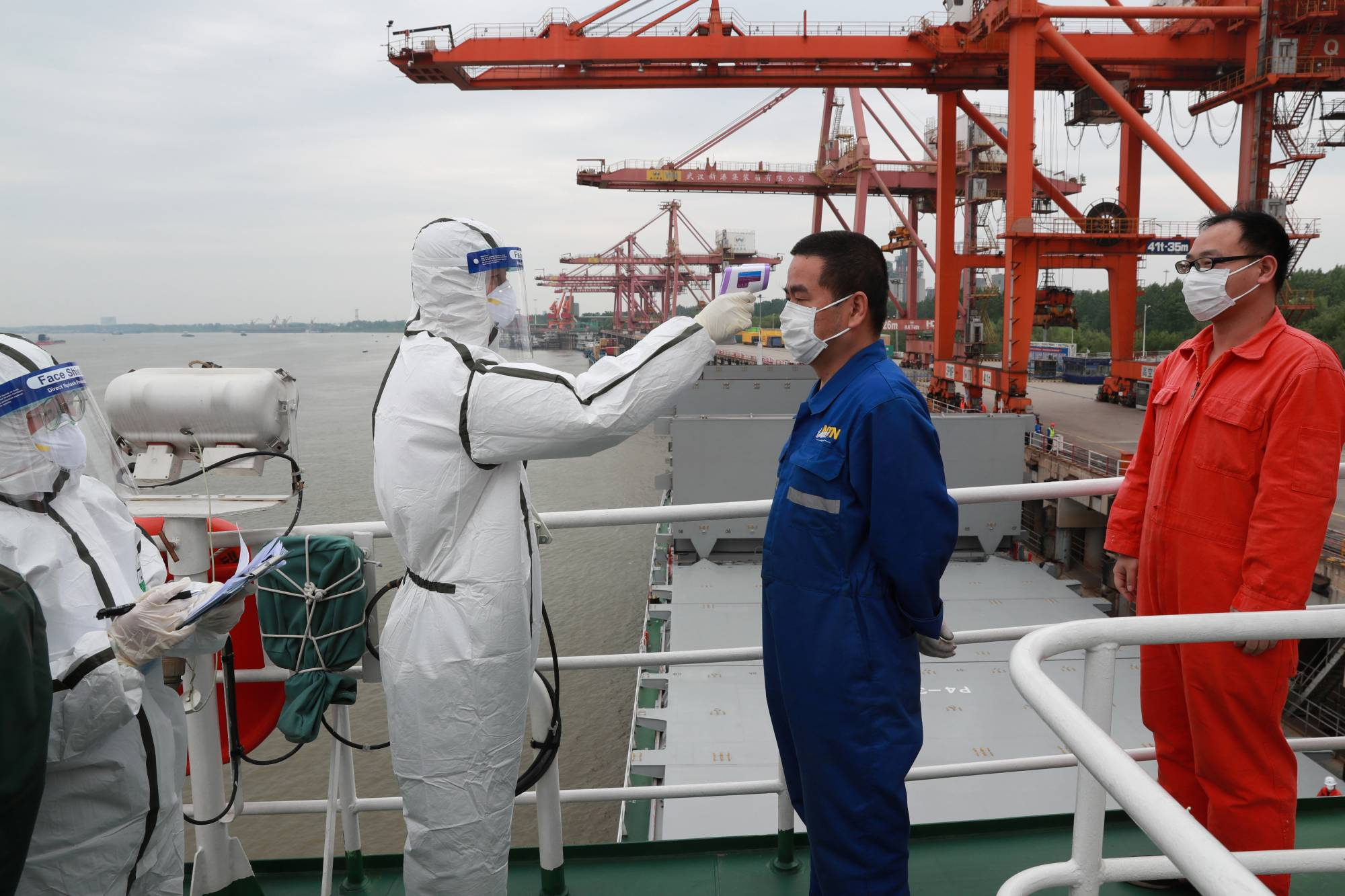 A person in a protective suit takes a body temperature measurement of a crew member of a cargo ship bound for Japan at a container terminal in the port in Wuhan, Hubei province, China, on Saturday.  | CHINA DAILY / VIA REUTERS
