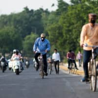 Commuters ride along a street in New Delhi on May 11. | AFP-JIJI