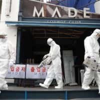 Quarantine workers Thursday spray disinfectant in front of a night club in the Itaewon neighborhood, following the coronavirus disease (COVID-19) outbreak in Seoul. | YONHAP / VIA REUTERS