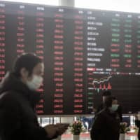 People wearing protective masks walk past an electronic stock board at the Shanghai Stock Exchange in Shanghai. Given the coronavirus pandemic, market participants are redrawing their long-term trading strategies.  | BLOOMBERG