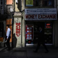 Pedestrians pass in front of a currency exchange location in Mexico City. Japan's Asset Management One Co. is aggressively seeking bond bargains in emerging markets. | BLOOMBERG