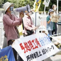 People protest Wednesday in Minato Ward, Tokyo, over moves by nuclear regulators to approve a nuclear fuel reprocessing plant in Rokkasho, Aomori Prefecture. | KYODO