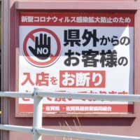 A pachinko parlor in the city of Saga displays a sign barring entry by people from outside the prefecture amid the coronavirus pandemic. | KYODO