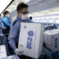 Boxes containing masks and other medical supplies are unloaded April 22 at Tokyo's Haneda Airport. The coronavirus pandemic has highlighted Japan's dependence on imported products, particularly from China. | ALL NIPPON AIRWAYS / VIA AP