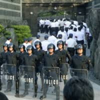 Riot police stand guard in front of the home of Kudokai leader Satoru Nomura as police raid the house on Sept. 11, 2014, in Kitakyushu. | KYODO